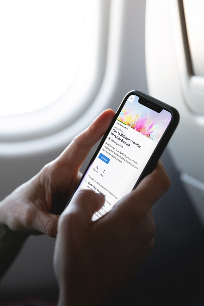 Kännykkä, jota pitelee kaksi kättä, taustalla lentokoneen ikkuna